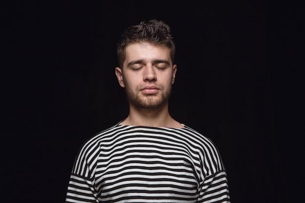 Close up ritratto di giovane uomo isolato. vere emozioni del modello maschile con gli occhi chiusi. premuroso. espressione facciale, natura umana e concetto di emozioni.