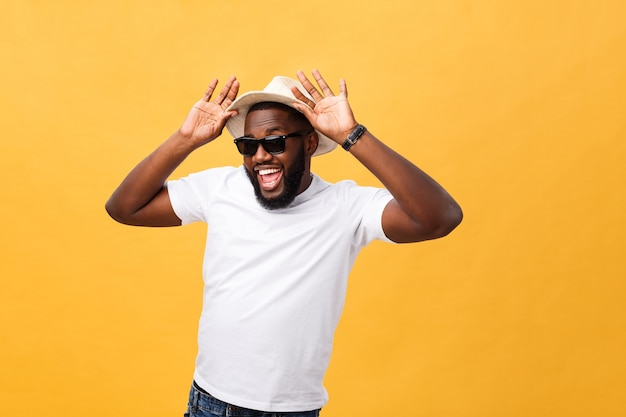 Close up portrait of a young man laughing with hands holding hat isolate