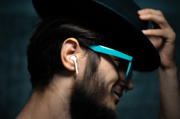 Close-up portrait of young man, listen the music with wireless earphones, wearing blue sunglasses and black hat, on dark background.