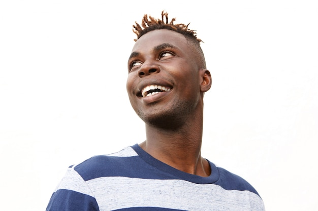 Close up portrait young man looking away and smiling against white background