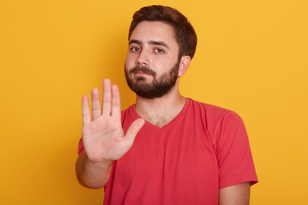 Close up portrait of young man requiring stop with his hand, handsome guy wearing red t shirt, showing stop gesture