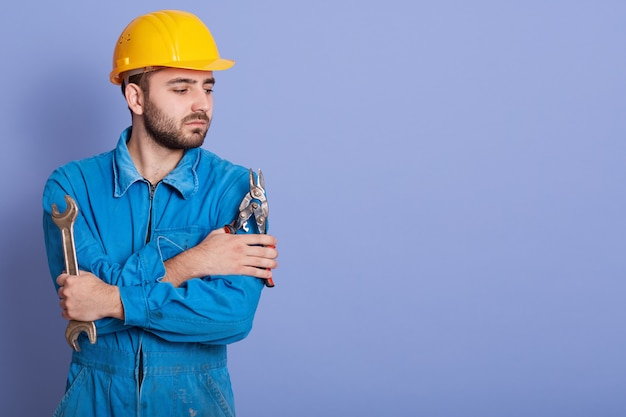 Close up portrait of young man wearing blue working clothes and yellow protective helmet