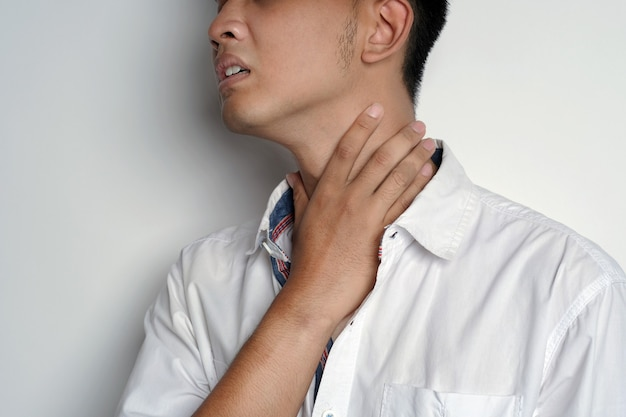 Close up portrait of young man wearing health mask having sore throat and touching his neck