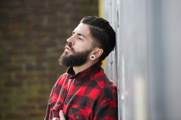 Close up portrait of a young man with beard standing outdoors alone