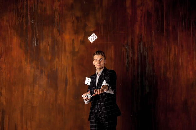 Close-up portrait of young man with gambling cards. handsome guy throws up  with card. clever hands of magician