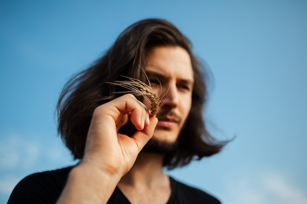Close-up portrait of young man with long hair holding wheat spike.