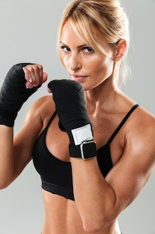 Close up portrait of a young muscular sportswoman boxing