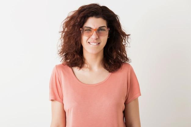 Chiuda sul ritratto di donna graziosa giovane hipster naturale con l'acconciatura riccia in camicia rosa in posa con gli occhiali isolati su sfondo bianco studio, faccia buffa, ammiccante