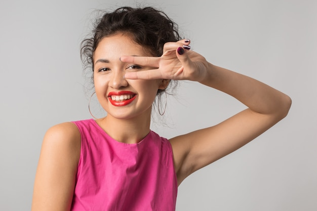 Close up portrait of young positive pretty woman in pink dress, showing peace sign, happy, smiling, summer style, red lipstick, fashion trend, flirty, , asian, mixed race, isolated