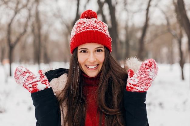 Ritratto del primo piano di giovane donna felice sorridente graziosa in guanti rossi e cappello lavorato a maglia che indossa cappotto invernale, passeggiate nel parco nella neve, vestiti caldi