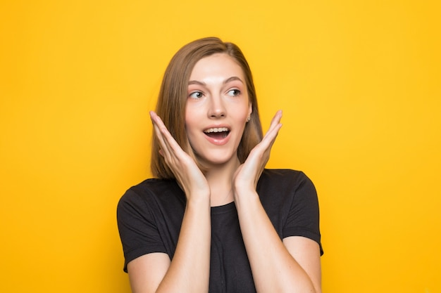 Close-up portrait of young pretty surprised woman with opened mouth standing with open palms on yellow wall