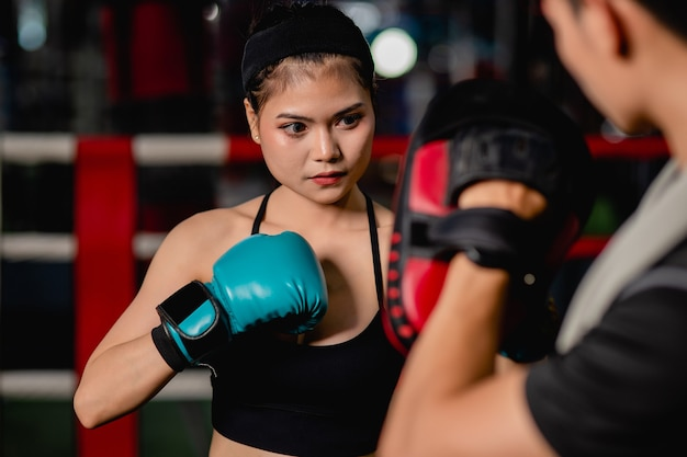 Ritratto ravvicinato giovane bella donna che si esercita con un bel trainer al corso di boxe e autodifesa sul ring di pugilato in palestra, lotta maschile e femminile recitazione, messa a fuoco selettiva e