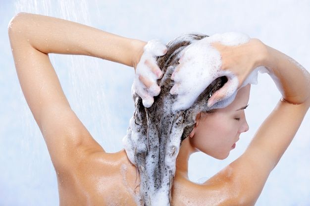 Close-up portrait of young pretty woman taking shower
