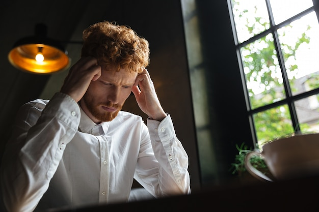 Close-up portrait of young redhead bearded overworked man in white shirt touching his head while sitting at office