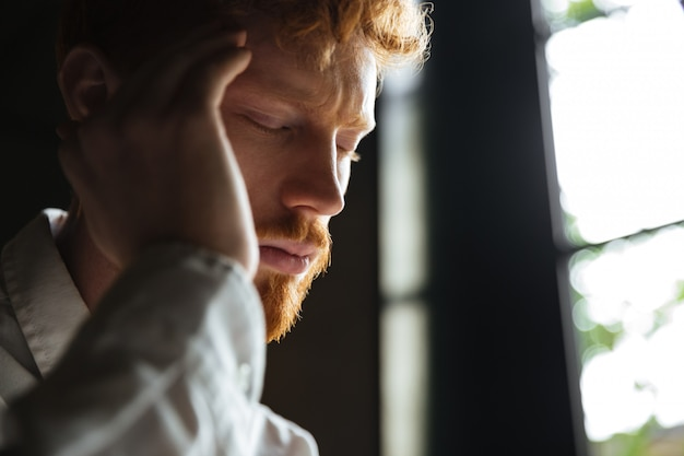 Close-up portrait of young redhead man with headache, touching his head