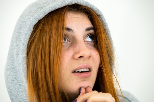 Close up portrait of young redhead woman wearing warm hoodie pullover praying holding hands together.