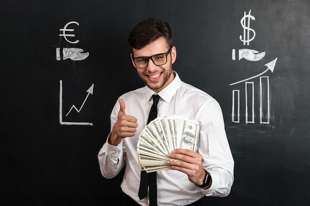 Close-up portrait of young smiling businessman holding bunch of money while showing thumb up gesture