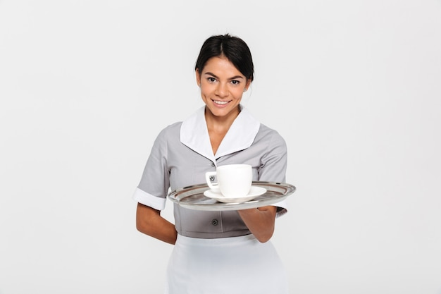 Close-up portrait of young smiling female waiter in uniform holding metal tray with cup of coffee
