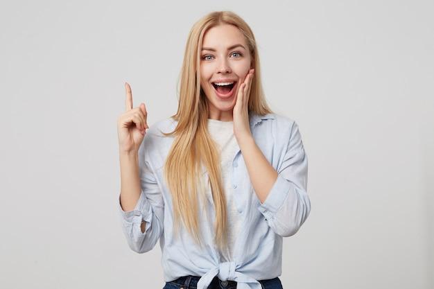 Close up ritratto di giovane donna sorridente in camicia blu tenendo il dito puntato verso l'alto, facendo il gesto di eureka con il dito indice, isolato