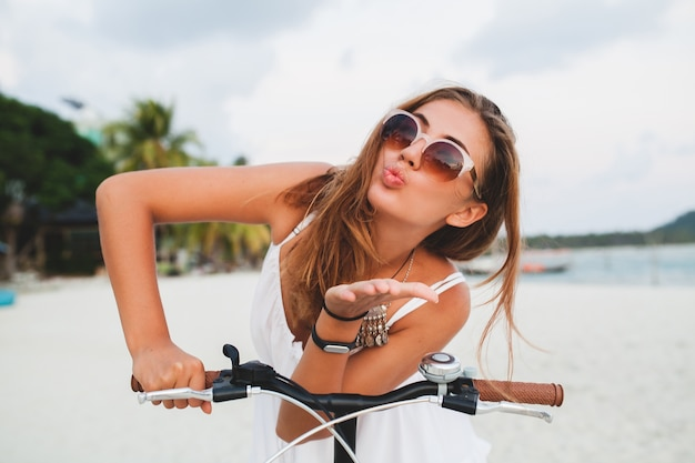 Close up portrait of young smiling woman in white dress riding on tropical beach on bicycle sunglasses traveling on summer vacation in thailand