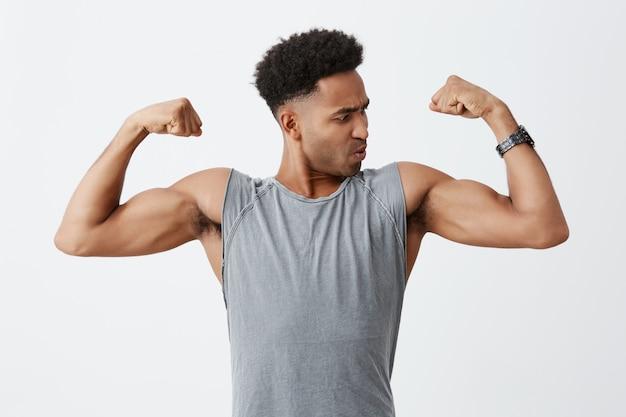 Chiuda sul ritratto di giovane uomo sportivo dalla pelle scura con l'acconciatura afro in camicia grigia che mostra i suoi muscoli, guardandolo con espressione del viso concentrato. salute e bellezza