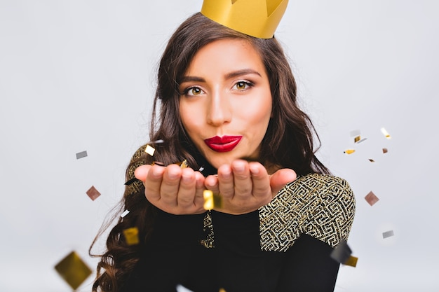 Close up portrait young stylish woman celebrating new year, wearing black dress and yellow crown, happy carnival disco party, sparkling confetti