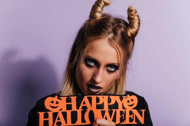Ritratto del primo piano di giovane strega con gli occhi azzurri. foto dell'interno della magnifica ragazza vampiro che celebra halloween.