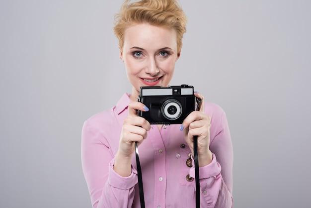 Chiuda sul ritratto sulla giovane donna che tiene vecchia macchina fotografica