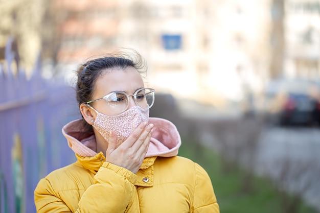 パンデミックコロナウイルスの間にマスクで肖像画の若い女性を閉じます。