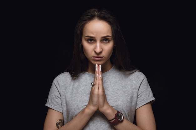 Close up portrait of young woman isolated on black studio background. photoshot of real emotions of female model. praying looking forward, sad and hopeful. facial expression, human emotions concept.