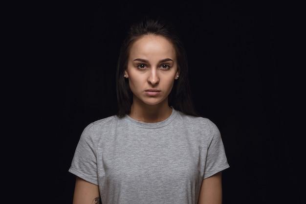 Chiuda sul ritratto di giovane donna isolata sulla parete nera dello studio