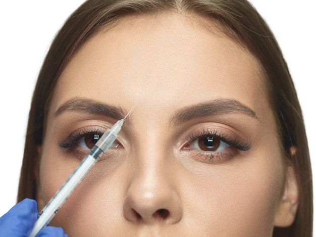 Close-up portrait of young woman isolated on white studio wall in filling surgery procedure