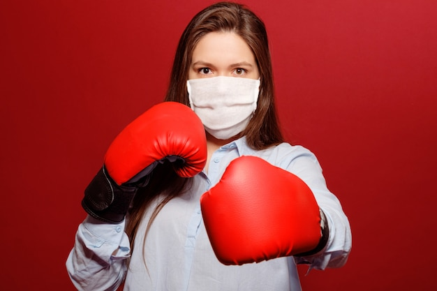 Close-up portrait of young woman in red boxing gloves on red background in protective medical mask, coronavirus pandemic, fight with virus