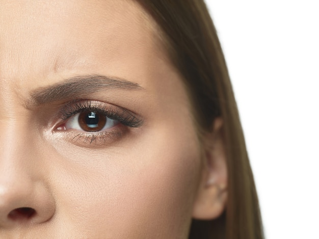 Close-up portrait of young woman's eyes and face with wrinkles.