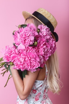 Close-up portrait of young woman in summer dress and straw hat holding peonies bouquet over her shoulder
