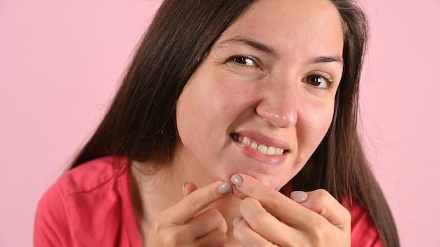 Крупным планом портрет молодой женщины несчастным прикосновением к ее коже, изолированной на розовом