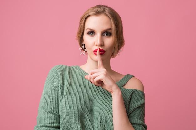Close up ritratto di giovane donna che indossa un maglione verde con labbra rosse sul rosa