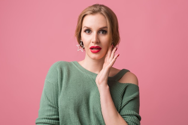 Close up portrait of young woman wearing a green sweater with red lips on pink