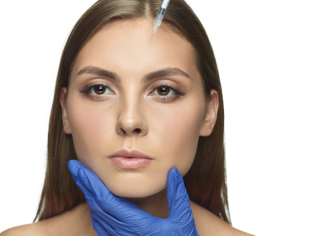 Close-up portrait of young woman on white studio background. filling surgery procedure. face contouring. concept of women's health and beauty, cosmetology, self-care, body and skin care. anti-aging.