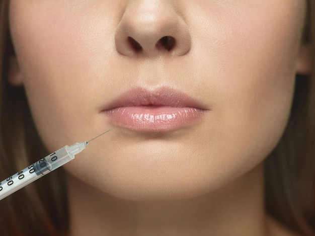 Close-up portrait of young woman on white  wall. filling surgery procedure. lip augmentation. concept of women's health and beauty, cosmetology, self-care, body and skin care. anti-aging.