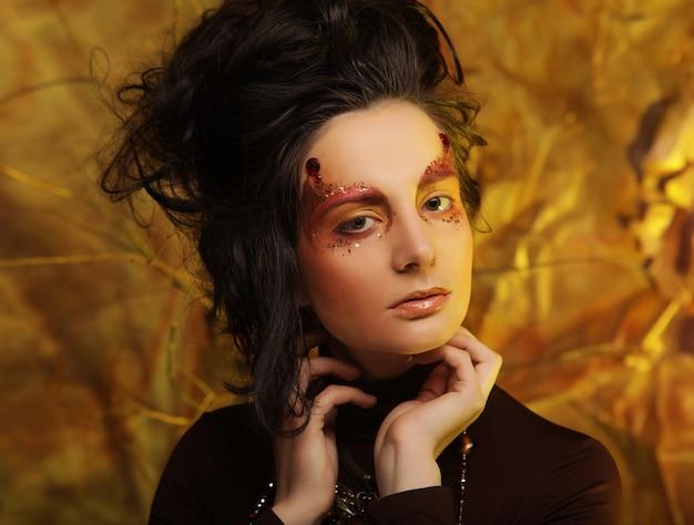 Крупным планом портрет молодой женщины с ярким творческим макияжем