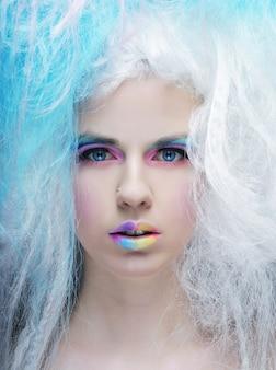 明るいメイクと創造的な髪の肖像若い女性を閉じる