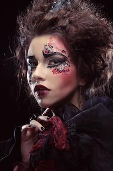 Закройте вверх по портрету молодой женщины с ярким макияжем, темой хэллоуина.