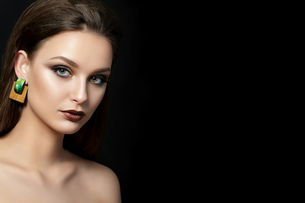 Close up portrait of young woman with brown lips and green smokey eyes over black background.