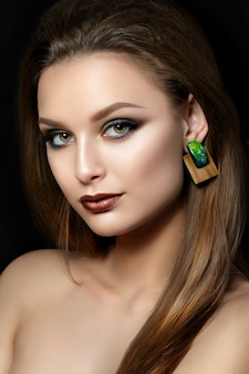 Close up portrait of young woman with brown lips and green smokey eyes. perfect eyebrows. modern fashion make up.