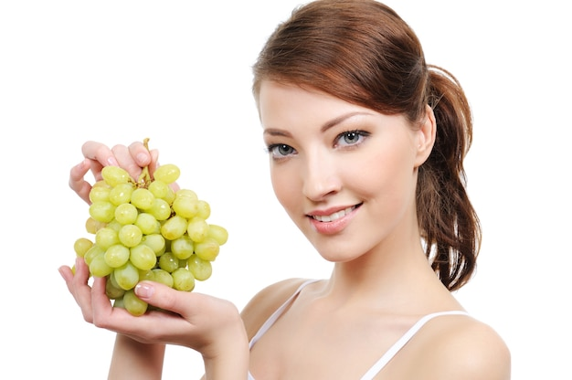 Close-up portrait of young woman with bunch of grapes