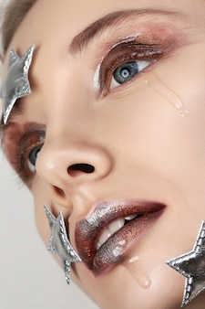Close up portrait of young woman with creative make up. crying little star. liquid glass, metallic glitters and smokey eyes.