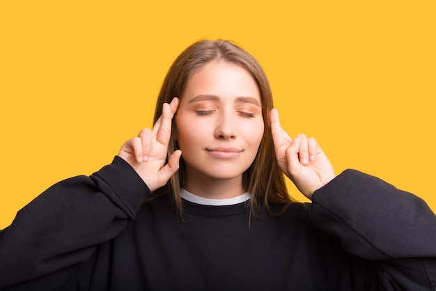 Close up portrait of a young woman with eyes closed crossing fingers.
