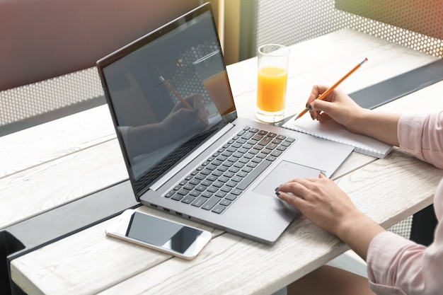 Close up portrait of a young woman working on laptop and writing, orange juice on the table.