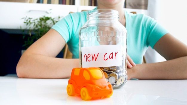 Close up portrait of young women in blue t-shirt sitting at the white table on which is located small orange car and ,full of coins, jar with the inscription new car